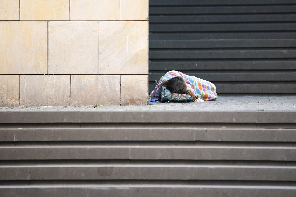 Eine Obdachlose schläft auf den Stufen vor der Frankfurter Kunsthalle Schirn.