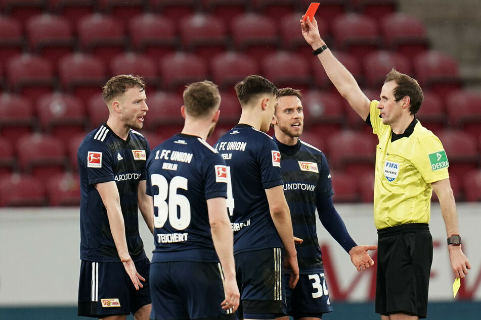 Schiedsrichter Sascha Stegemann (r.) zeigt Unions Nico Schlotterbeck (M) die Gelb-Rote-Karte. Florian Hübner (l.) und Marcus Ingvartsen