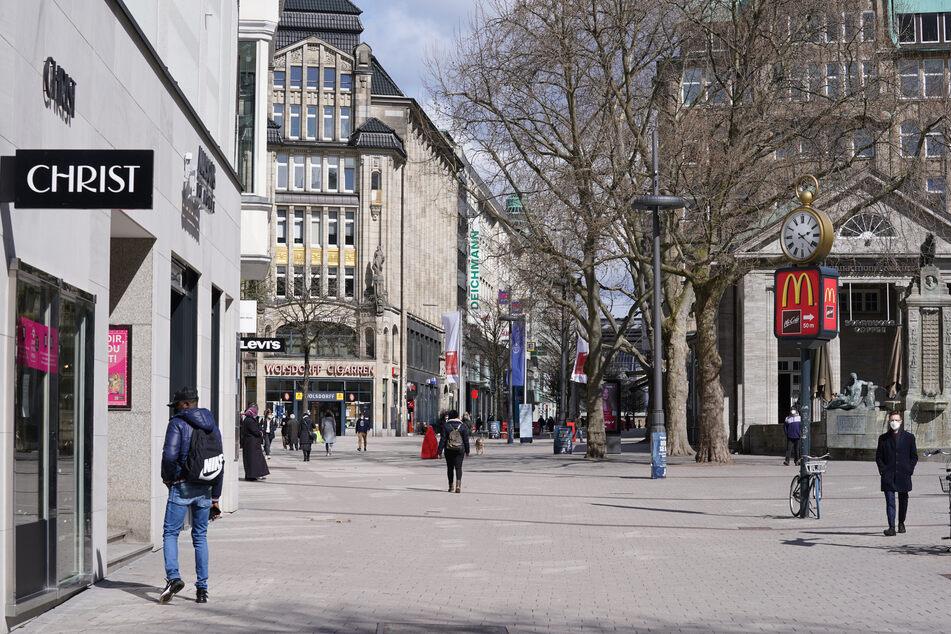 Passanten gehen durch die Einkaufsstraße Spitalerstraße in der Innenstadt. Der Einzelhandel darf unter strengen Auflagen wieder öffnen.