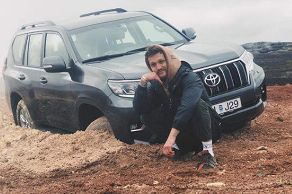 Alexander Tikhomirov posiert lächelnd vor seinem verunglückten Wagen.