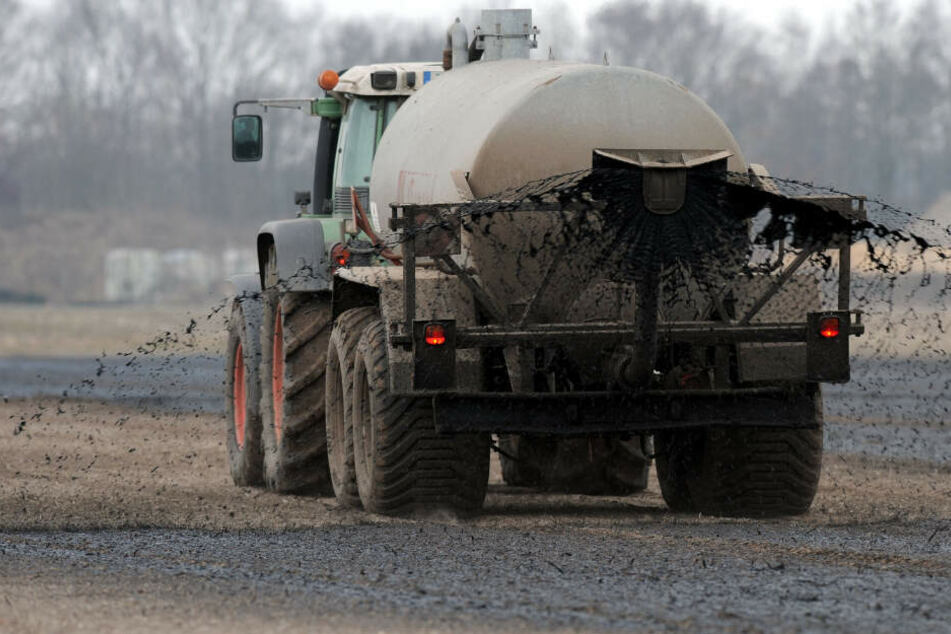 Mit einem Traktor wird ein Güllewagen über ein Feld gezogen: Die aufsteigenden Gase können für Menschen gefährlich werden.