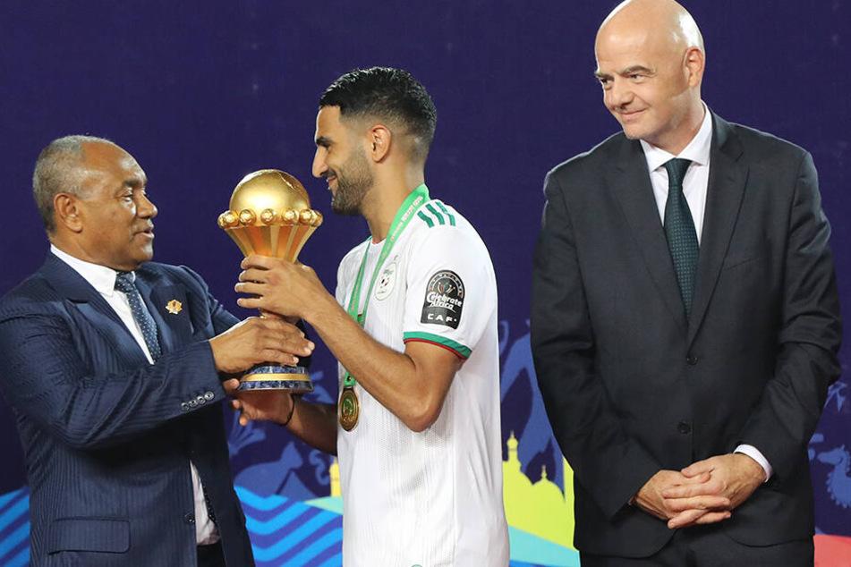 Riyad Mahrez erhält von CAF-Präsidenten Ahmad Ahmad die Afrika-Cup-Trophäe. Nach einem Freistoßtreffers in der fünften Minute der Nachspielzeit gewann Algerien mit 2:1 gegen Senegal.