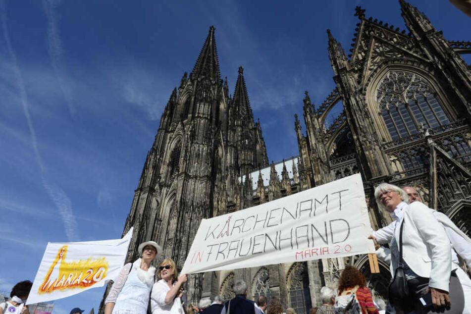 """Demonstrantinnen der Bewegung """"Maria 2.0"""" stehen mit einem Transparent mit der Aufschrift """"Kirchenamt in Frauenhand - Maria 2.0"""" vor dem Kölner Dom."""