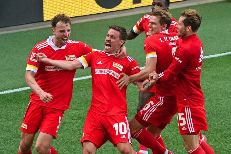 Die Union-Kicker feiern gemeinsam mit Torschütze Max Kruse (2.v.l.) den späten 2:1-Siegtreffer gegen RB Leipzig am letzten Spieltag der vergangenen Bundesliga-Saison, der ihnen die Qualifikation für die UEFA Conference League ermöglicht hat.