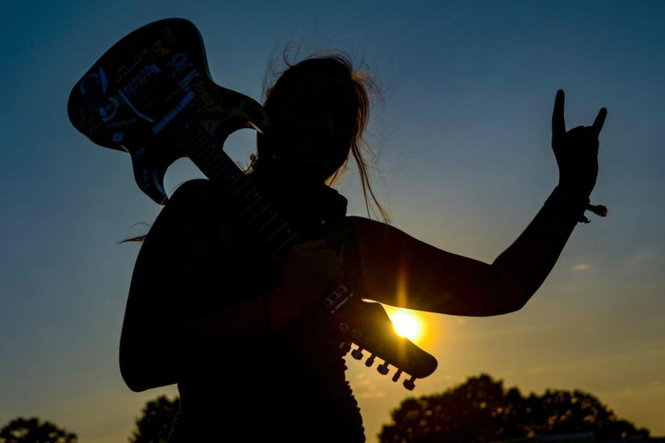 """Eine Frau mit einer E-Gitarre auf der Schulter zeigt beim Wacken Open Air auf dem Festivalgelände den Metalgruß, die sogenannte """"Pommesgabel""""."""