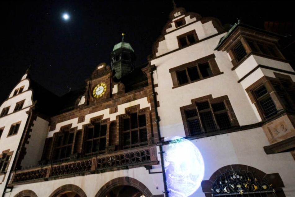 März 2018: Eine Weltkugel wird aufs dunkle Rathaus von Freiburg geworfen.