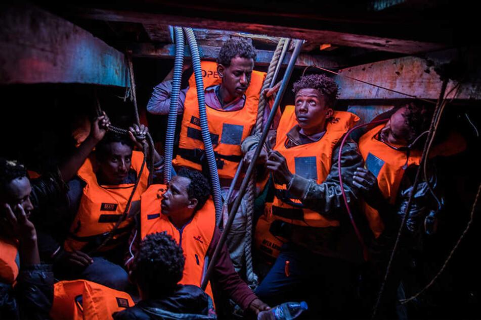 Mehrere Flüchtlinge aus verschiedenen afrikanischen Ländern sitzen an der Küste zu Libyen im unteren Bereich eines überfüllten Holzbootes und warten auf Rettung.