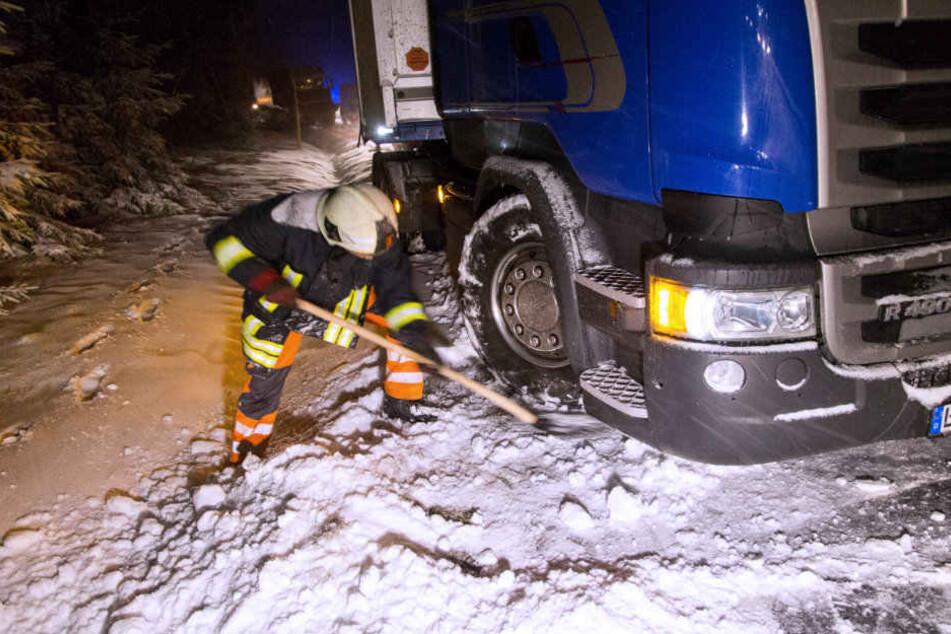 Ein Feuerwehrmann versucht einen Lkw zu befreien.