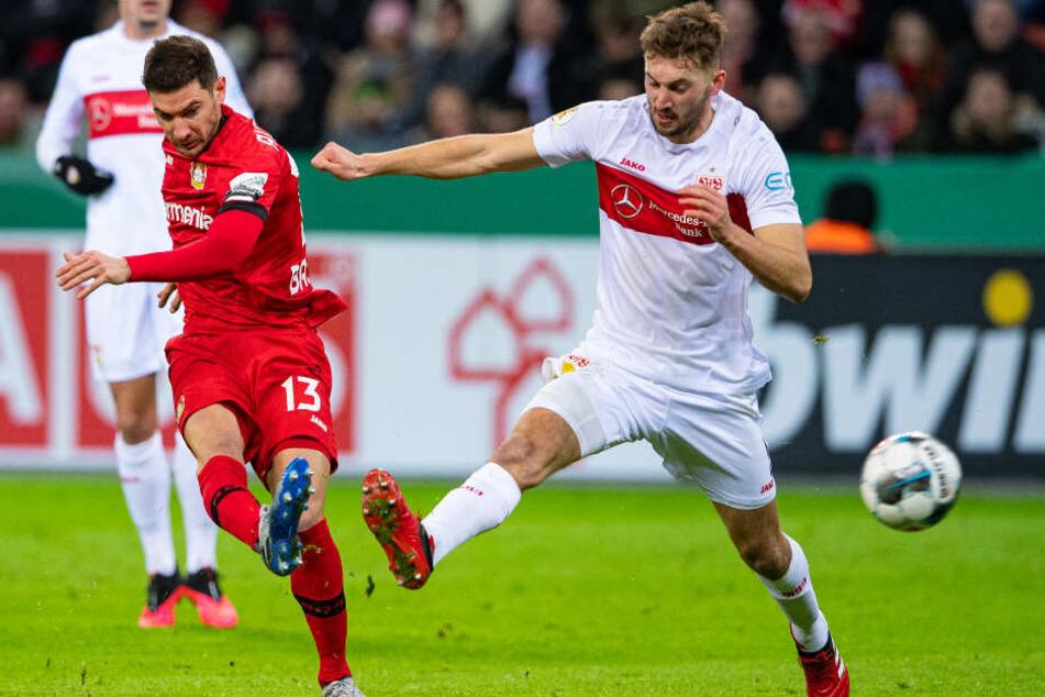 Leverkusens Lucas Alario (l) schießt den Ball gegen Stuttgarts Nathaniel Phillips auf das Tor.