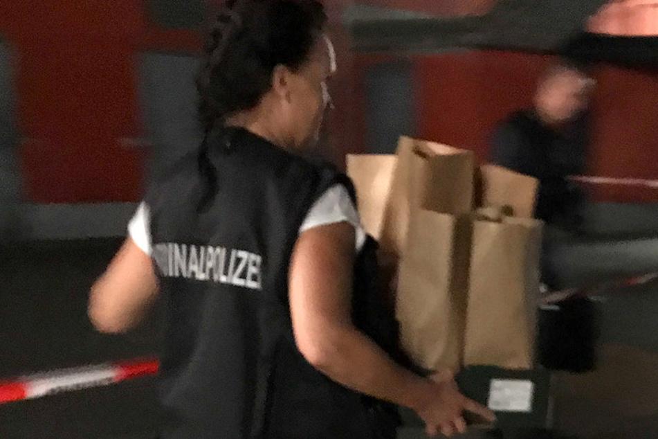Eine Kriminalpolizistin trägt Beweismaterial vom Tatort weg.