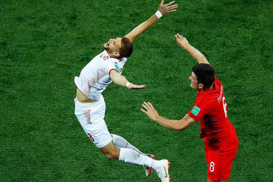 Ist das noch Fußball oder was? Der Tunesier Rami Bedoui (l) macht nach einem kleinen Schubser seines englischen Gegenspielers Harry Maguire (r.) den sterbenden Schwan.