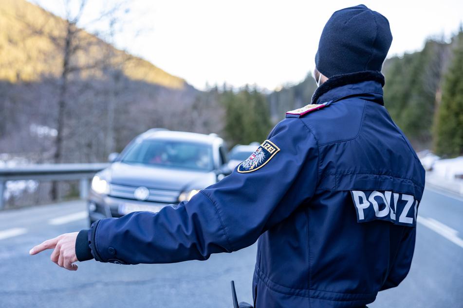 Ein Polizist kontrolliert Fahrzeuge auf der Pass-Thurn-Straße in Kitzbühel, Österreich kurz vor der Landesgrenze zu Salzburg.