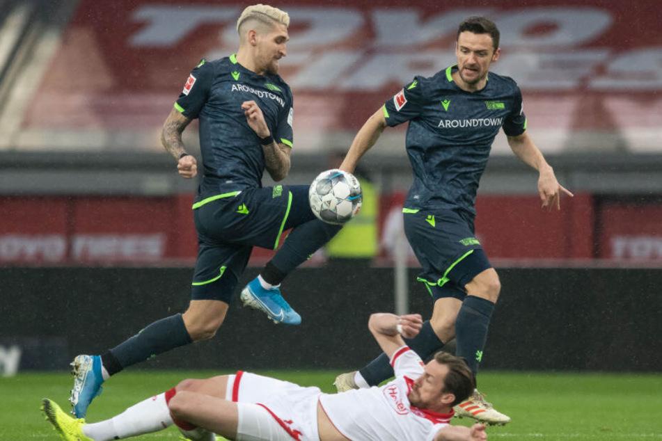 Düsseldorfs Adam Bodzek und Robert Andrich (l) und Christian Gentner (r) von Union versuchen an den Ball zu kommen.