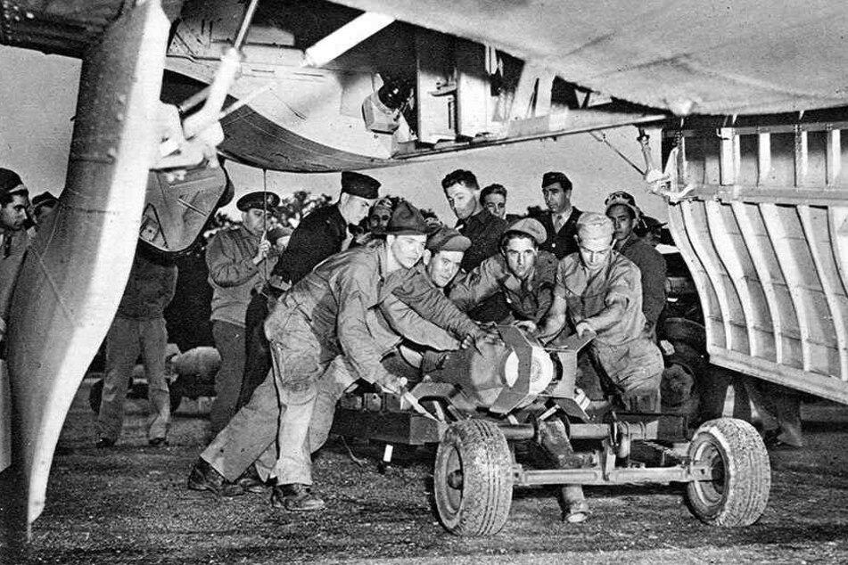 Bodentruppen rollen einen Wagen mit einer Bombe unter ein Kampfflugzeug in Position.