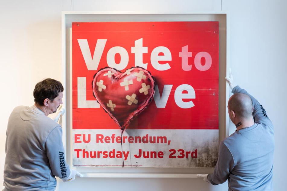 """Mitarbeiter richten bei einer Pressevorbesichtigung im Münchner Büro vom Auktionshaus Sotheby's das Werk """"Vote to love"""" von Banksy aus."""