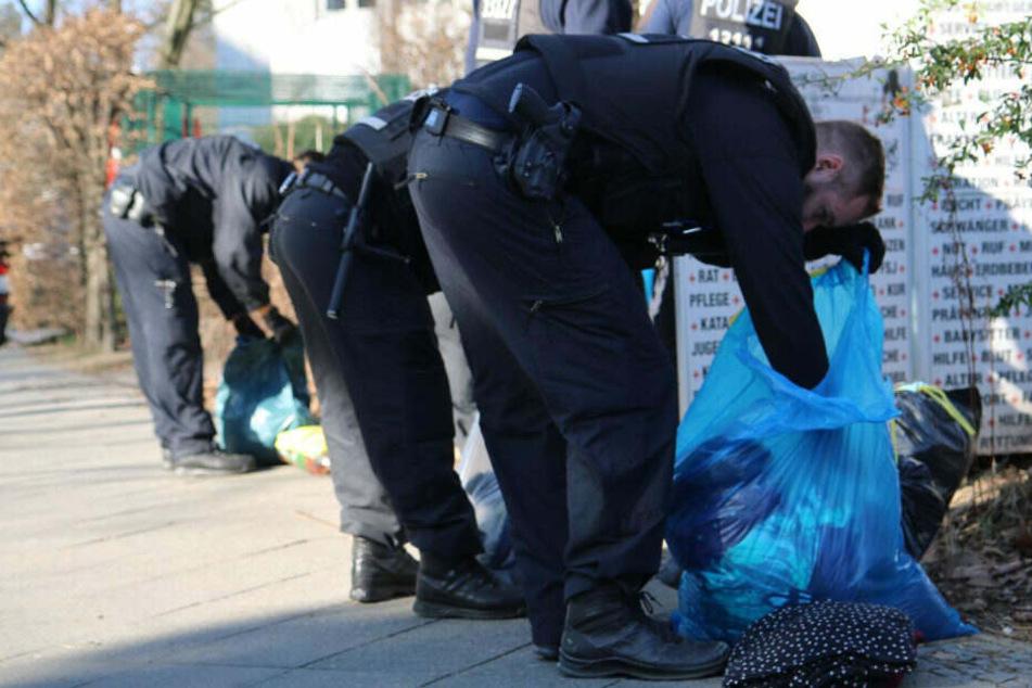 Polizisten durchsuchen die Beutel.