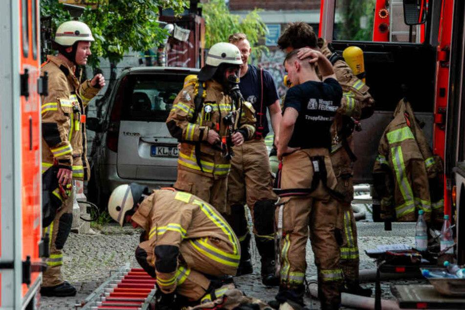Feuerwehrmänner stehen nach dem Einsatz an der Straße Am Flutgraben in Kreuzberg.