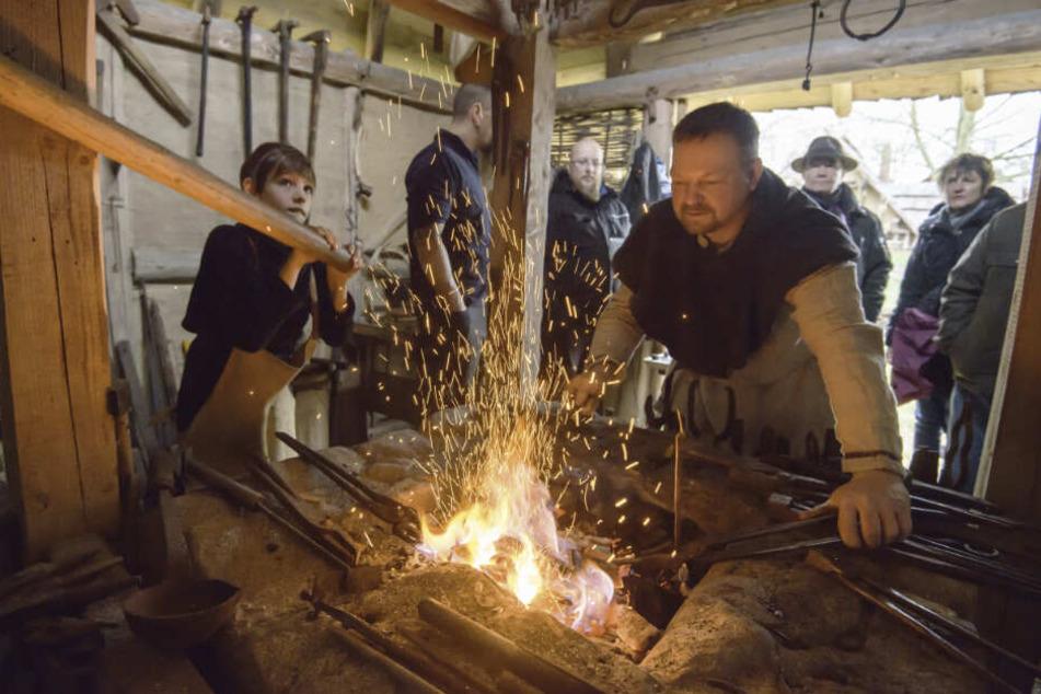 Ins neue Jahr geschmiedet: Matthias Sengenberger (51) zeigt, wie Schmieden im Mittelalter war. Leon (9, l.) am Blasebalg versorgt das Feuer mit Luft.