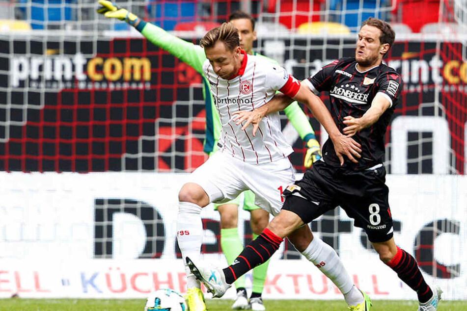 Der Düsseldorfer Adam Bodzek (l) und Stephan Fürstner von Union Berlin kämpfen um den Ball.