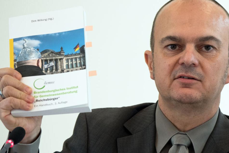 Der Leiter des Brandenburger Verfassungsschutzes, Frank Nürnberger, zeigt während einer Pressekonferenz ein Handbuch zum Umgang mit den sogenannten Reichsbürgern.