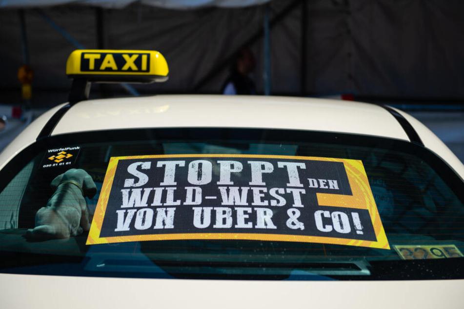 Ein Taxi mit einem Protestschild steht in Berlin am Rand einer Demonstration gegen den Fahrdienstanbieter Uber.