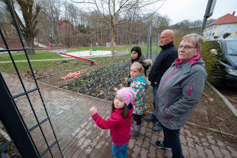 Ingrid Börner (65), ihre Enkel und andere Anwohner warten seit April auf den Tag, an dem der Zaun zum Spielplatz wieder verschwindet.