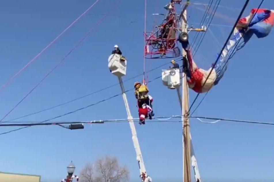 A firefighter helps Santa down from his sleigh, which is tangled in the power lines.