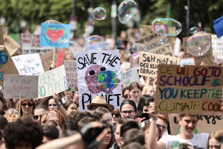 Schüler demonstrieren mit Protestplakaten während des Fridays for Future - Klimastreiks für die Umsetzung der Pariser Weltklimaabkommens.