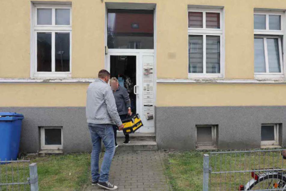 Kriminalbeamte verlassen nach der Spurensicherung durch die eingetretene Tür den Tatort.