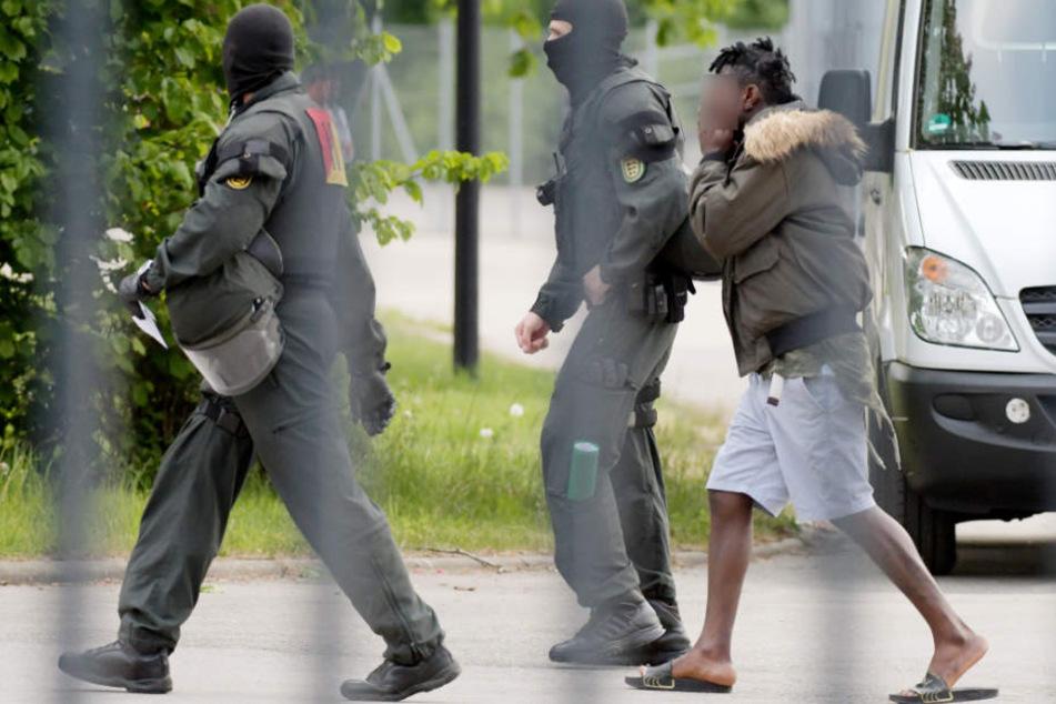 Maskierte Beamte eskortieren einen Mann.