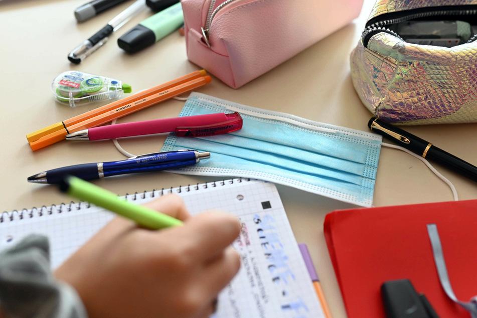 Eine Mund-Nase-Schutzmaske liegt zwischen Schreibutensilien auf einem Tisch, während ein Schüler einen Stift über einem Schreibblock hält.