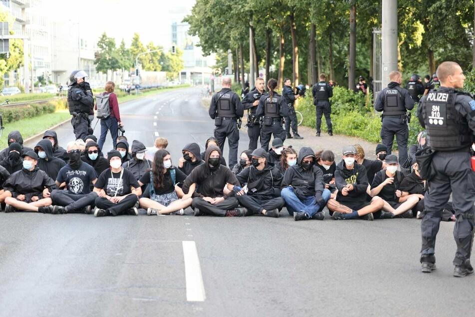 Die Gegendemonstranten versperren in Form einer Sitzblockade den Ring.