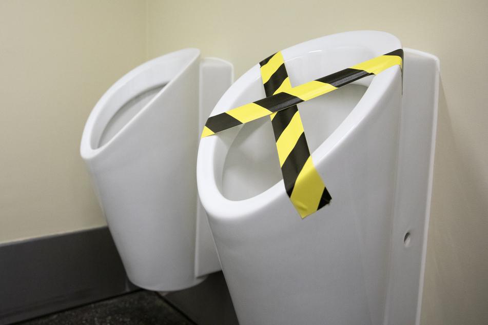 Eines der Urinale ist mit Absperrband abgeklebt, um einen Mindestabstand bei der Benutzung zu gewährleisten.
