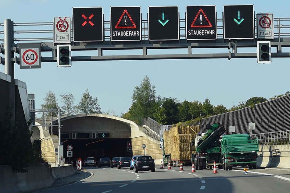 Ein mit Stroh beladener LKW und Einsatzfahrzeuge der Polizei stehen auf der A113. Der LKW war mit seiner Ladung im Tunnel stecken geblieben.