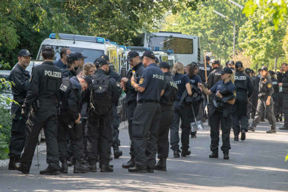 Polizisten sammeln sich auf einer Straße, um anschließend weiter in einem Forst bei München nach den zwei Leichen zu suchen.