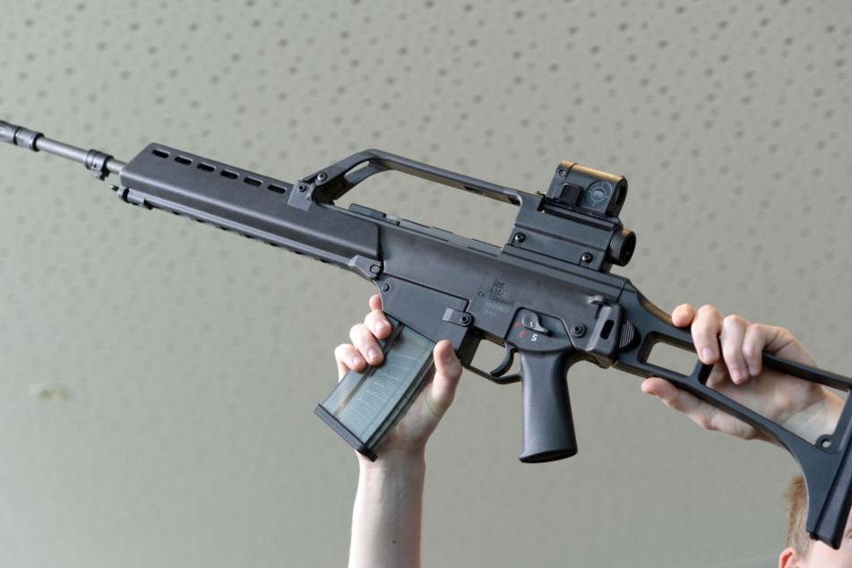 Ein Mann hält in der Firmenzentrale ein Sturmgewehr G36 von Heckler und Koch in die Höhe. (Symbolbild)