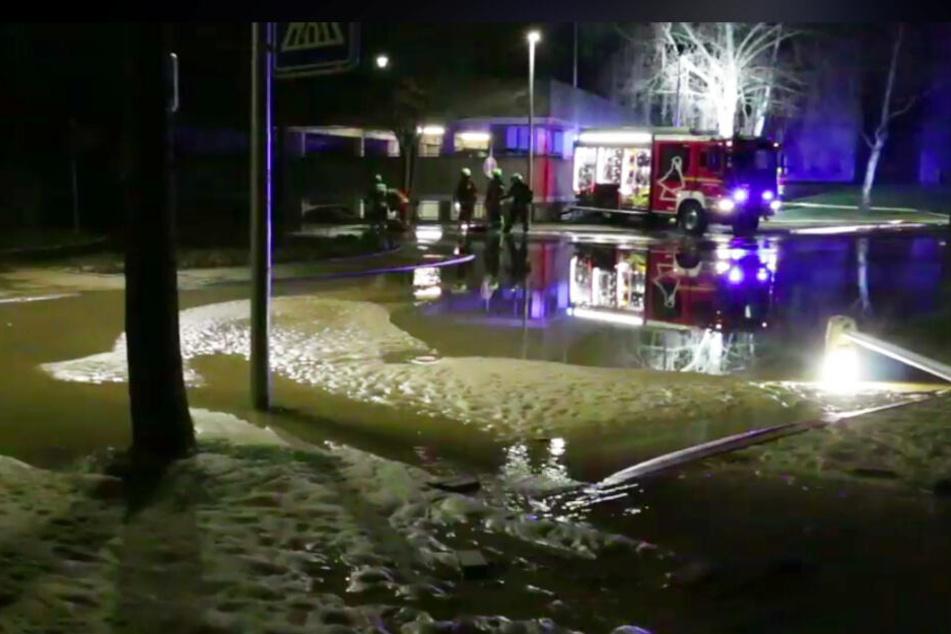 Eine Straße in Lüneburg ist mit Wasser und Sand überflutet, die Feuerwehr pumpt dagegen an.