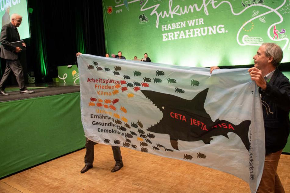 Winfried Kretschmann (links im Bild) geht auf dem Landesparteitag der Grünen in Sindelfingen von der Bühne und passiert Demonstranten.