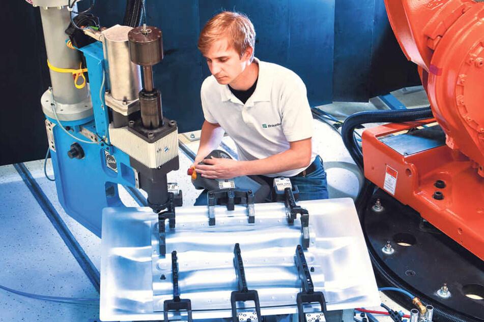 Das geht bisher nur am Fraunhofer-Institut: Mitarbeiter Christian Kraus  arbeitet Hand in Hand mit einem Industrieroboter.