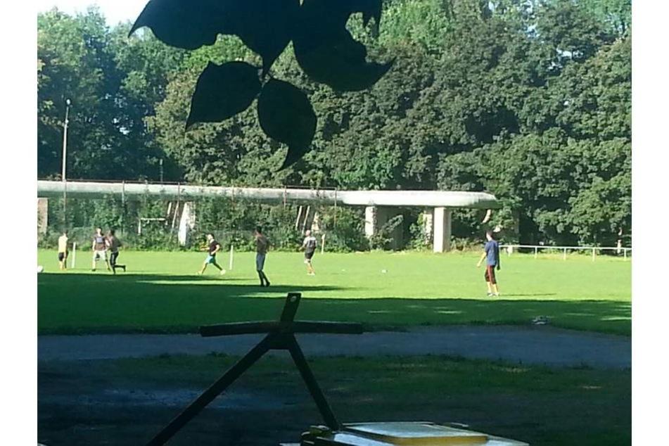 Illegales Fußballspiel in Markersdorf: Junge Männer klettern über den Zaun zum Kicken.