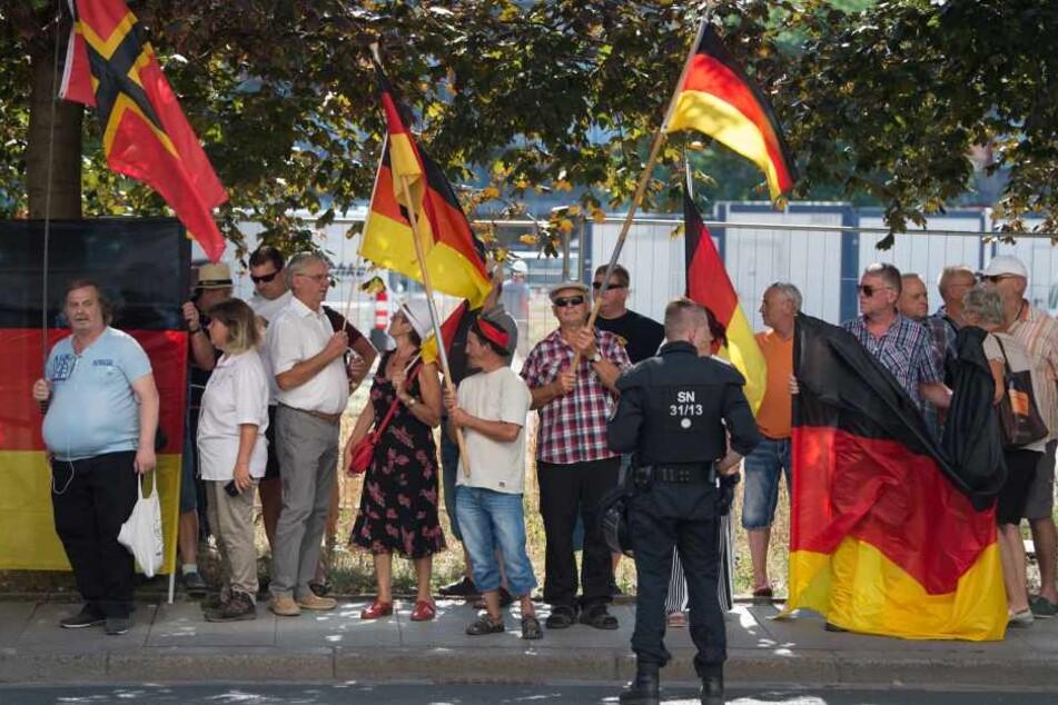 Am Rande des Merkel-Besuches demonstrierten ein paar hundert PEGIDA und AfD-Anhänger. Ein Teilnehmer ging dann auf ein TV-Team los.