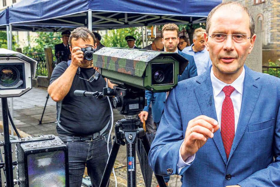 Innenminister Markus Ulbig (53, CDU) neben einer gewöhnlichen Kamera  (Camouflage-Optik) und der neuen Laser-Kamera in Weiß.