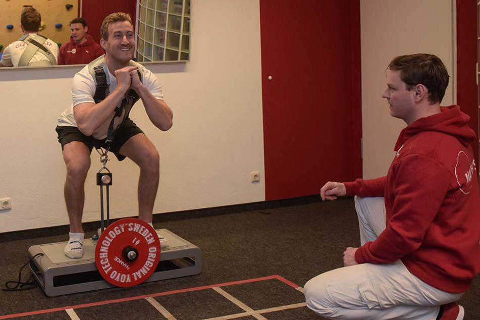 Harrison Reed trainiert auf diesem Gerät die Kraft. Er muss sich unter Aufsicht von Physiotherapeut René Wallner hochdrücken und anschließend gegen den Druck wieder in die Hocke nach unten bewegen.