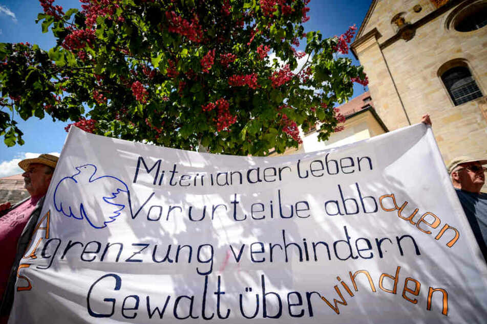 """Teilnehmer einer Mahnwache halten ein Plakat hoch. Die Gruppe """"Mahnwache Ellwangen"""" kritisiert den Polizeieinsatz in der Flüchtlingsunterkunft Ellwangen."""