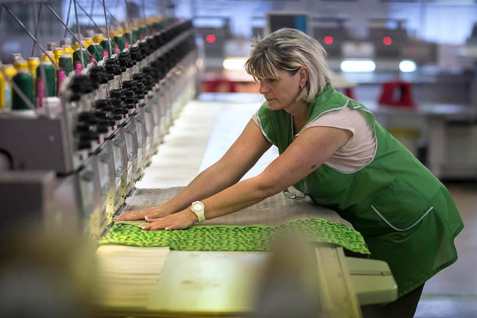 Wichtige Handarbeit: FunkeMitarbeiterin Gerlind Lange (56) richtet den Stoff an einem Mehrkopf Stickautomat.