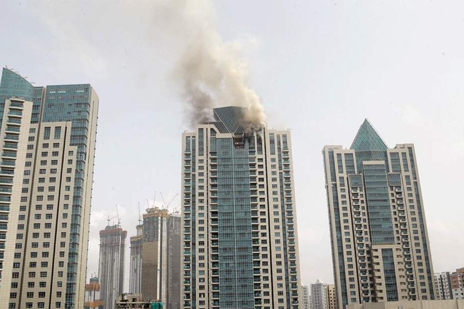 Rauch und Flammen steigen von dem Wohnturm «Beau Monde Tower» auf.