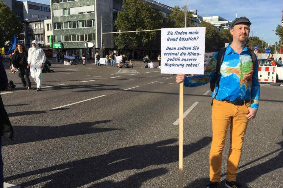 Marco Schlich steht mit seinem Schild auf der Straße.