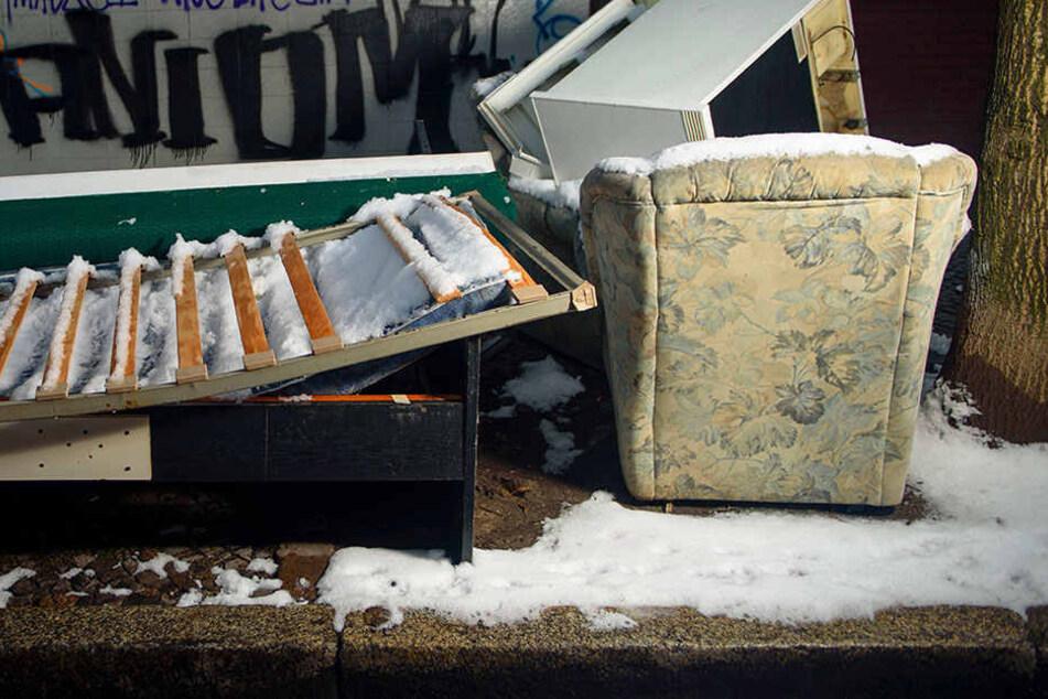 Ein altes Sofa, ein Sessel und ein Bettgestell mit Lattenrost liegen auf einem Gehweg in Berlin-Neukölln im Schnee.