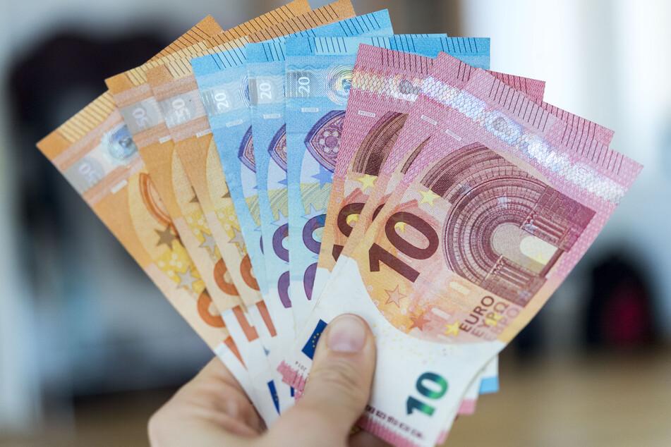 Eine Frau hält Banknoten von 10, 20 und 50 Euro gefächert in der Hand. (Symbolbild)