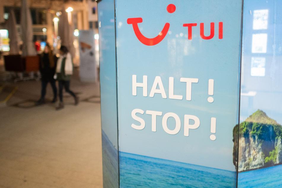 """Die Worte """"Halt! Stop!"""" stehen vor einem TUI-Reisebüro. Der Reisekonzern hat mit einem dramatischen Rückgang der Buchungen zu kämpfen."""